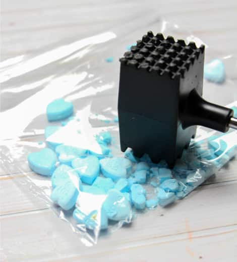 Using a mallet to crush the candies into a powder