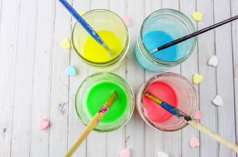 The mixed conversation heart paints in mason jars with paintbrushes in them