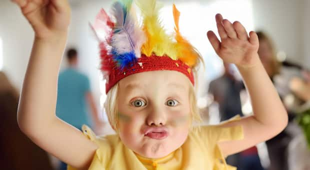 A little boy dressed in costume with a headdress