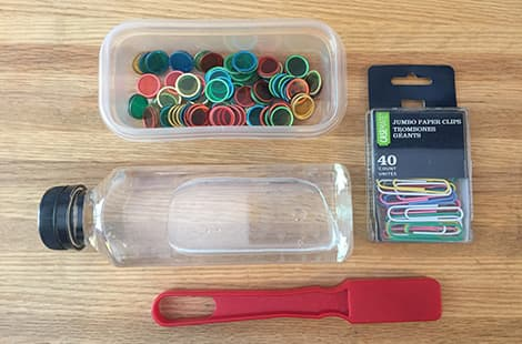 Magnetic wand, plastic bottle, and bingo chips in a plastic container.