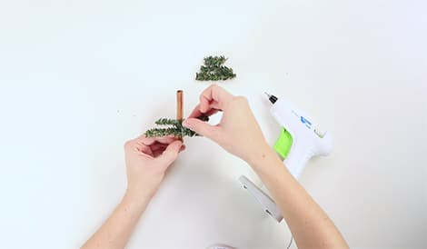 gluing greens to cinnamon stick