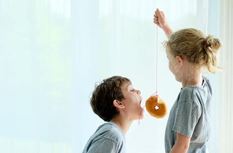 Little girl holds up doughnut for boy to chew.