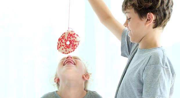 Boy holds up doughnut on a string for sister.