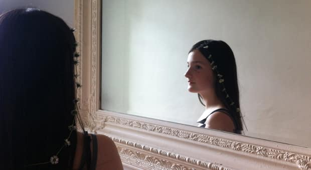 A young girl looking in the mirror