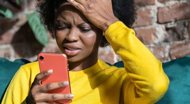 Black woman looks at her phone with confused look.