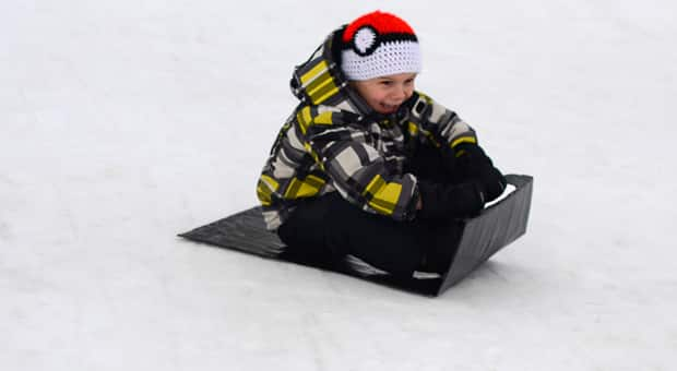 A little boy having fun going down a hill on a duct tape sled