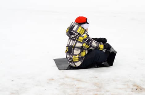 A little boy going down a hill on a duct tape sled