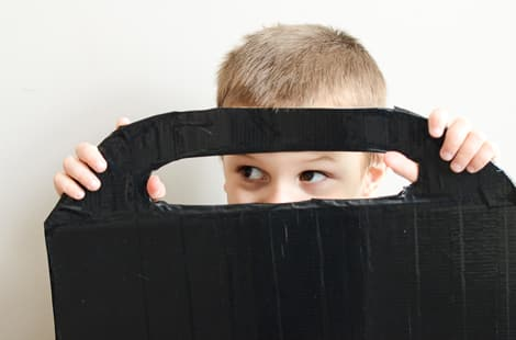 A little boy peeking out from the opening where the handle of the duct tape sled is