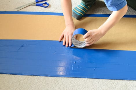 A child using blue duct tape on their piece of cardboard