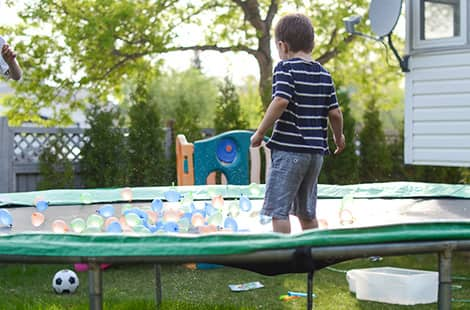 Little boy bounces on trampoline with water balloons on it.