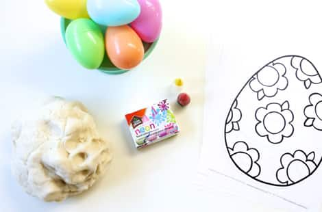 White play dough beside neon food colouring on a table with a bowl of plastic eggs and printable sheet