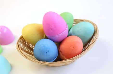 Plastic Easter eggs in a basket, each filled with dough that matches the plastic egg's colour