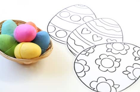 Play dough filled eggs in a basket alongside laminated egg mats