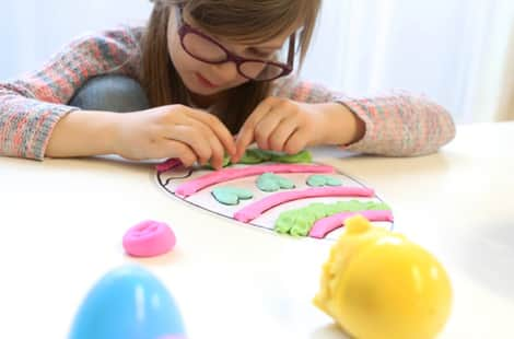 Little girl decorating an egg mat with colouful play dough