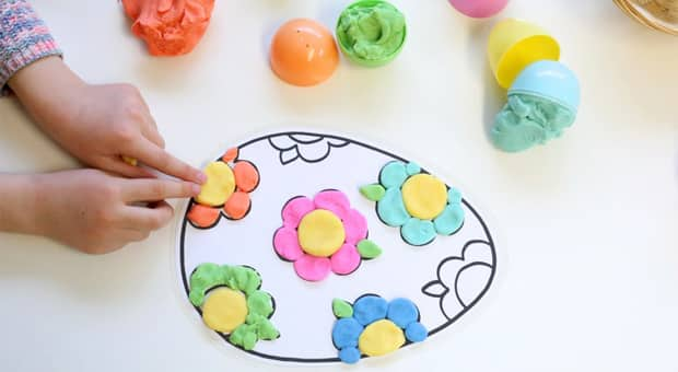 Little girl pressing colourful play dough onto an Easter egg mat