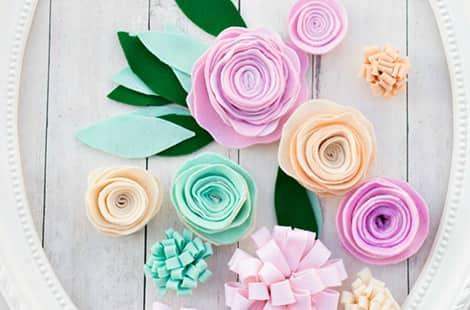 Pastel-coloured felt flowers in frame.