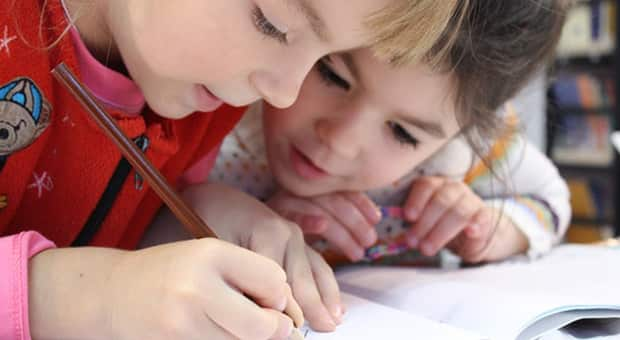 Two little girls look over notebook
