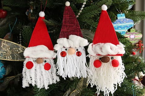 completed fabric Santa ornaments hanging on the tree