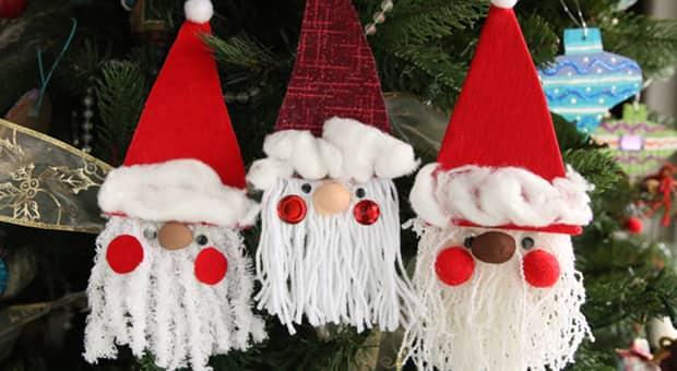 Three fabric scrap Santa ornaments hanging on a Christmas tree