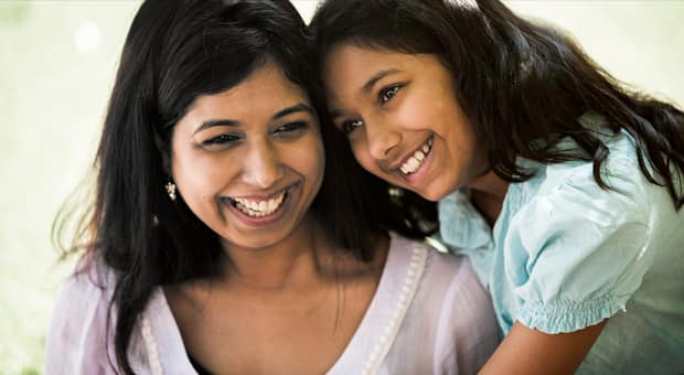 A mother and daughter of colour laugh together