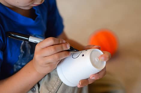 kid drawing on a styrofoam cup with a marker to make a ghost face