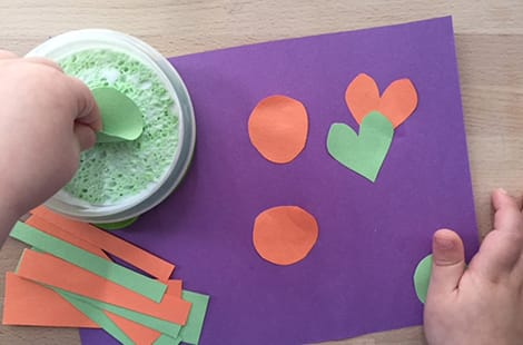 Child dips construction paper in glue-y sponge in container.
