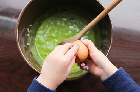 Cracking an egg into green mixture.