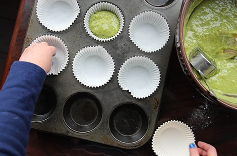 Lining muffin tray with liners.