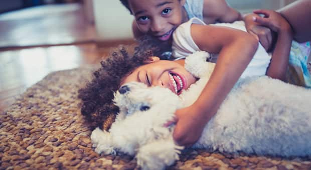 Two children playing with their dog