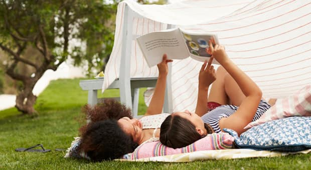 A mother and daughter lying outside in a blanket fort reading a book
