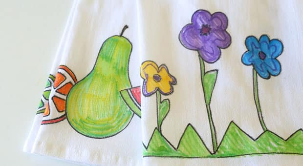 Colourful drawings of flowers and fruit on a dish towel.