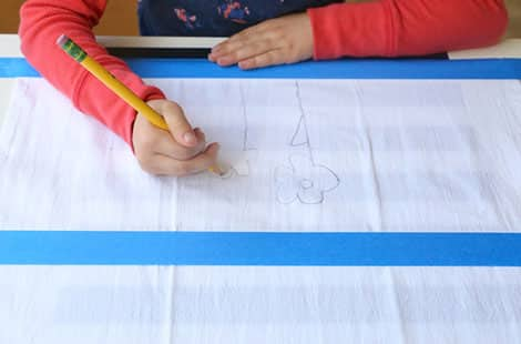 Child does a pencil drawing on a dish towel.