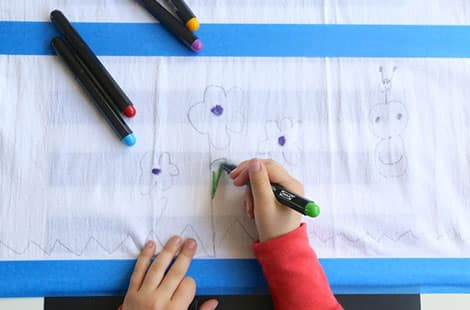 Using fabric markers to colour in pencil drawings.