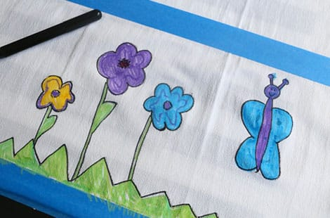 Black fabric marker is used to outline child's drawing to make it pop.