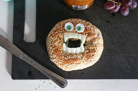 A bagel with googly eyes and vampire teeth!