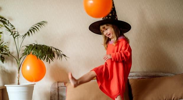 Little girl dressed as a witch having fun kicking orange balloons