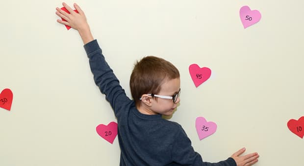 A little boy placing his hand on a foam heart on the wall with numbers written on them