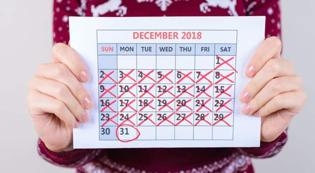 Someone holding up a calendar with December 31st circled in red marker