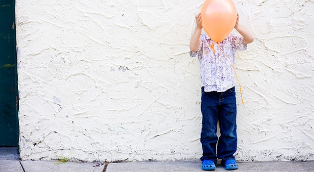 Child holds balloon in front of their face.