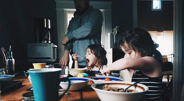 Father in the background while daughters eat cereal