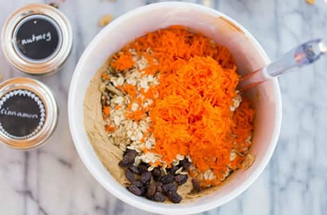 Shredded carrots, oats, nuts and raisins in bowl.