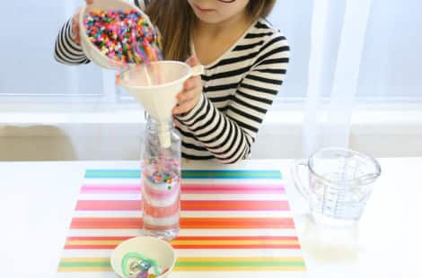 Pouring colourful beads into the I Spy bottle