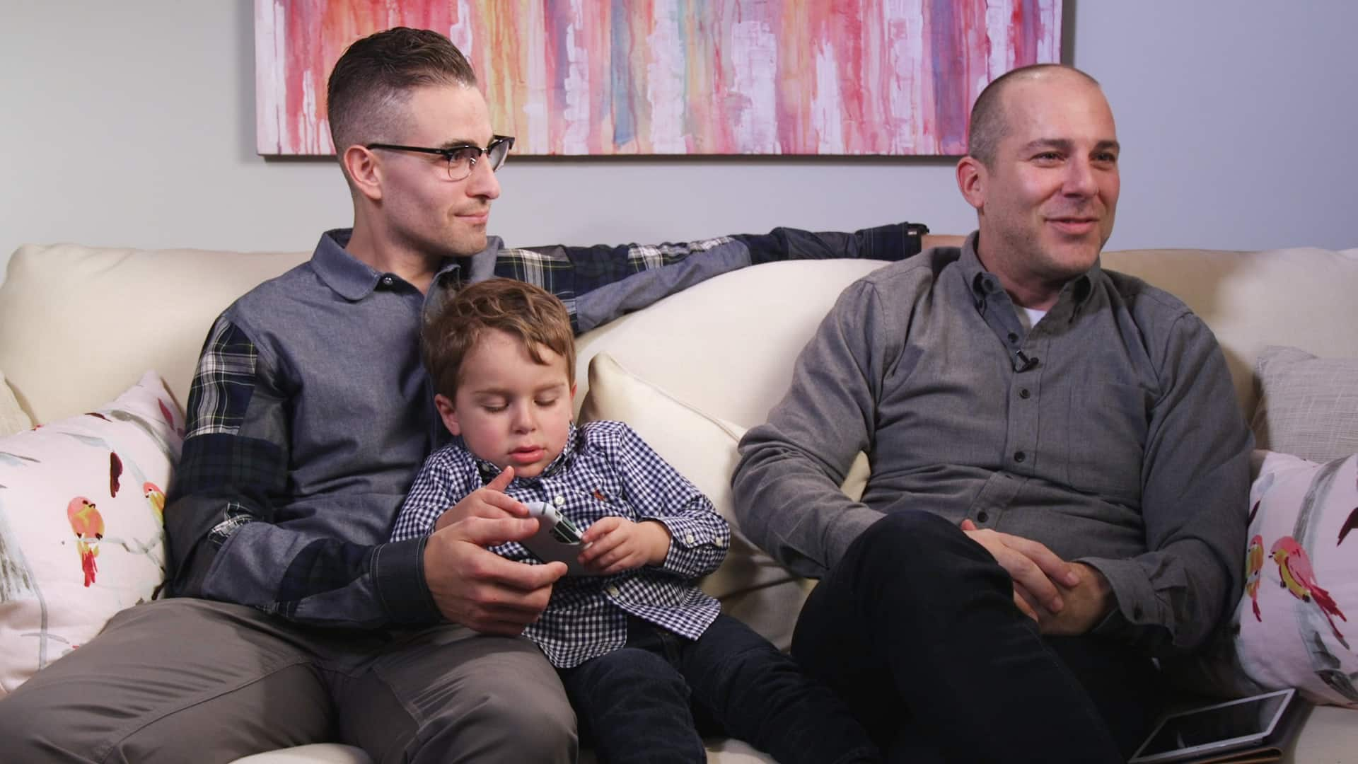 Two fathers with their young son, sitting on the couch.