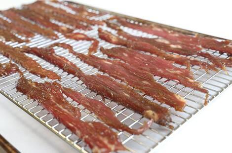 Meat strips set on oven-safe baking rack.