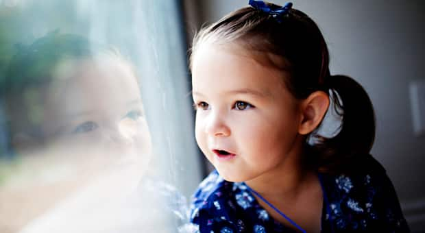 little girl smiling and looking out window
