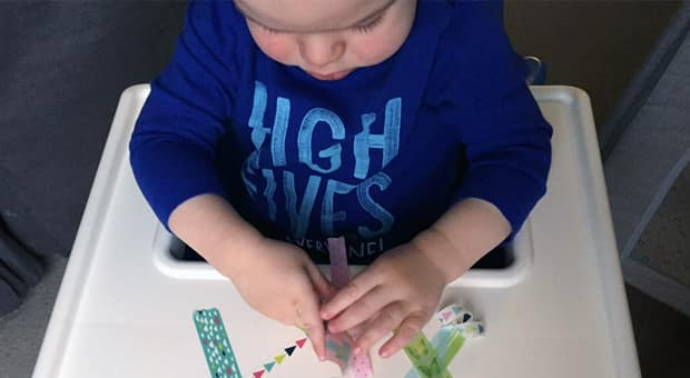 a young child plays with tape