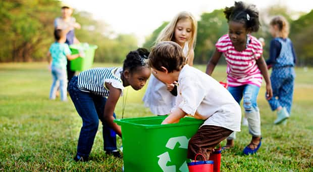 A bunch of kids picking up recycling and garbage from a green space