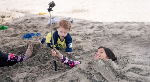 A young girl buried in sand and vlogging on the beach