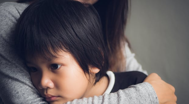 A child looking concerned being hugged and comforted
