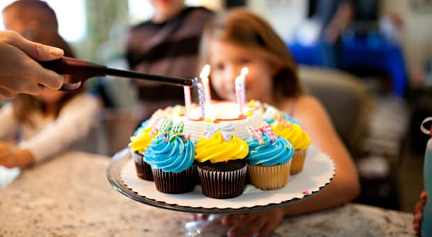 A birthday cake being lit with children in the background